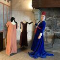 [Translate to it:] Mittelalterliche Frau gekleidet in blauem Kleid mit rotem Hut. Daneben zwei weitere Kleider in lachs und braun.