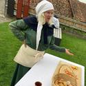 [Translate to it:] Mittelalterlich gekleidete Frau präsentiert Essen aus der damaligen Zeit.