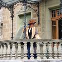 [Translate to it:] Galante Dame auf dem Balkon von Schloss Hünegg.
