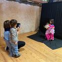 [Translate to it:] Mädchen verkleidet in pinkem Prinzessinenkostüm. Mutter und Bruder schauen zu.
