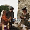 [Translate to it:] Marktstand aus dem Mittelalter mit drei Personen vor dem Schloss Spiez.
